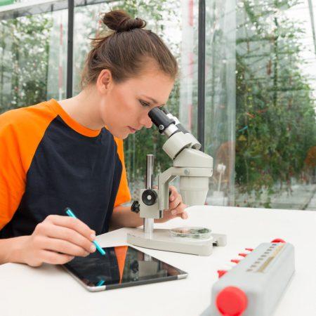 Op de afbeelding is het volgende afgebeeld: Een dame die door een microscoop kijkt. Op de achtergrond staat een plantenkas afgebeeld.