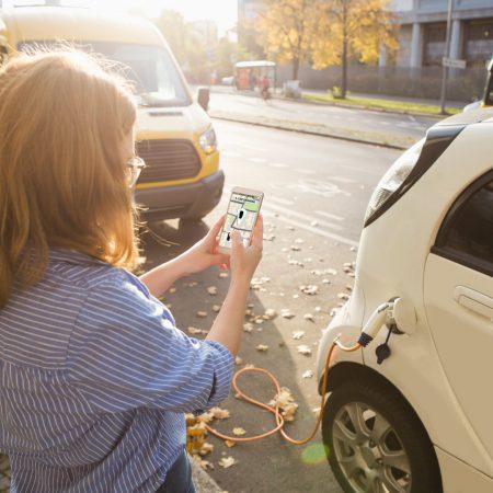 Op de afbeelding is het volgende afgebeeld: Een elektrische deelauto. De dame die naast de auto staat, kan via een applicatie op haar telefoon de auto huren.