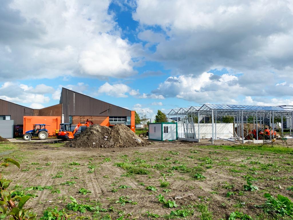 Uitzicht op terrein van Verse Grond met de plantenkas in aanbouw
